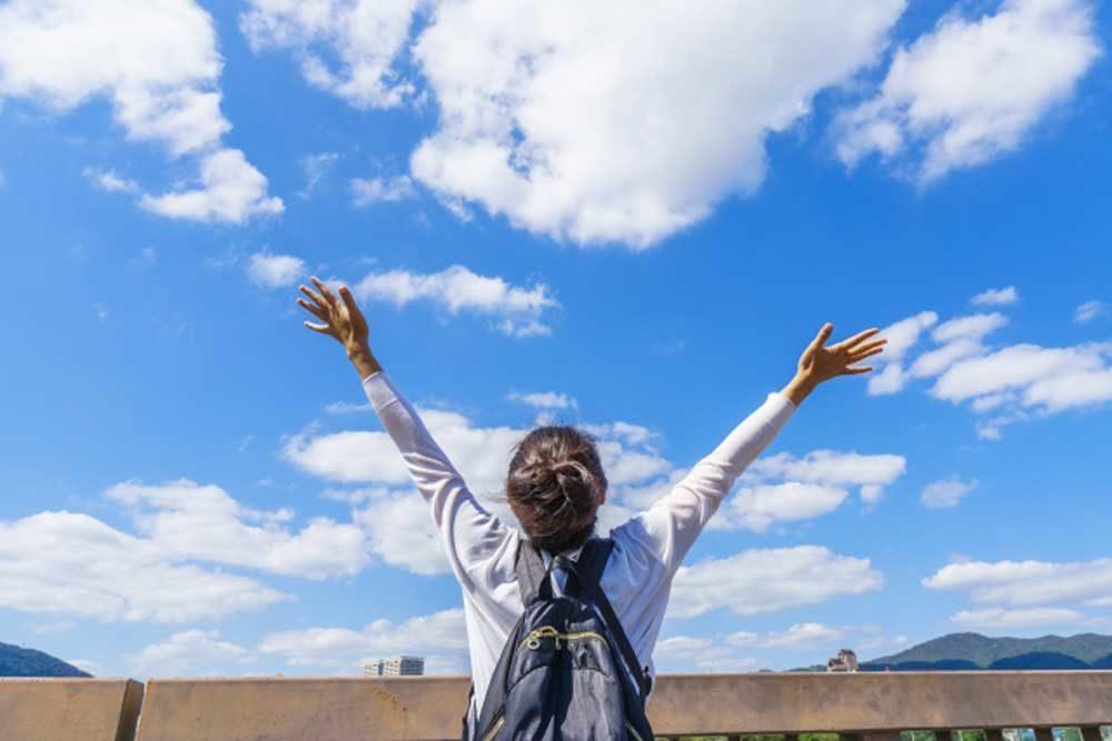 大空の下で喜ぶ人